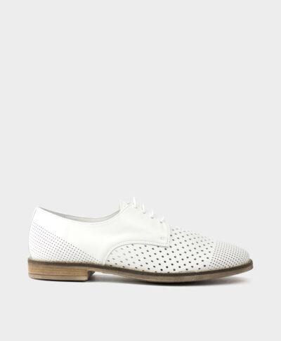 Zapato plano de cordones en piel vacuna troquelada en blanco.