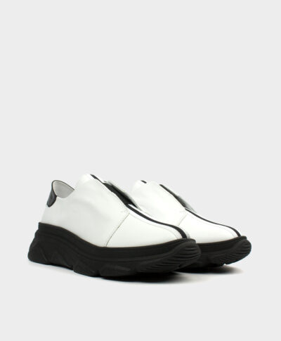 Vista de frente de las zapatillas deportivas con piso grueso negro en piel vacuna blanca con cierre elástico en negro.