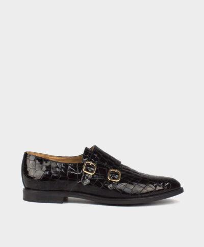 Zapato monk plano en piel vacuna acabada en charol cocodrilo en tono negro.